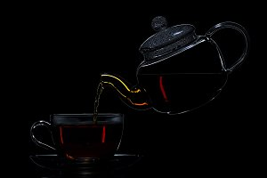 Transparent teapot with black tea on a black background