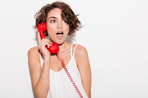 Shocked young lady talking by red retro telephone.