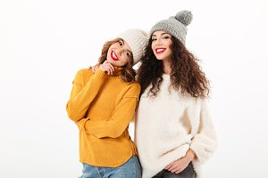 Two smiling girls in sweaters and hats posing together