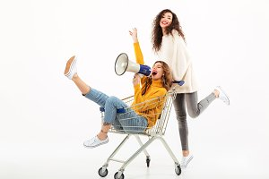 Two happy girls in sweaters having fun with shopping trolley