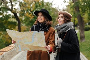 Portrait of two pretty girls dressed in autumn clothes