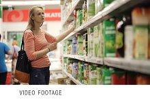 Woman chooses juice in supermarket