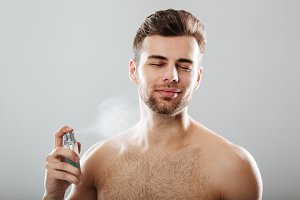 Portrait of a handsome half naked man spraying perfume