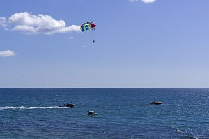 Men on a parachute over the sea