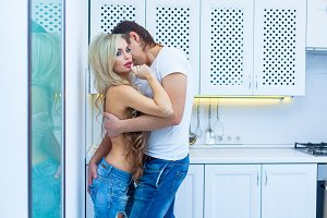 Beautiful young passionate couple is smiling and hugging before having sex in kitchen at home