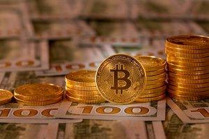 Bitcoins stacked on new design 100 dollar bills
