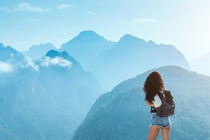 Beautiful young tourist girl with backpack at mountains