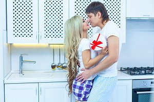 St. Valentine's day love. 14 February. Handsome young man giving present to beautiful woman at home in the kitchen