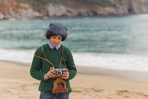 Boy with vintage camera at the beach.