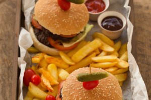 hamburgers with french fries, tomato and barbeque sauce