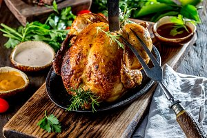 Roasted chicken with rosemary served on black plate with sauces on wooden table, close up