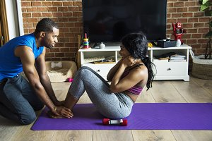 Black couple exercise at home