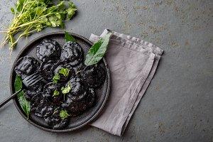 Traditional Italian black ravioli on black plate, gray stone slate background. Top view