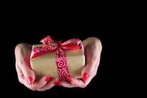 women's hands hold a gift box with r