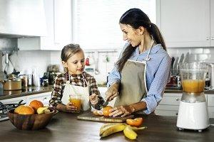 Daughter helps mom in preparing food
