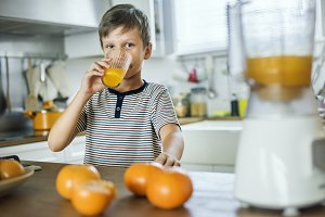 Young Caucasian boy drinking orange