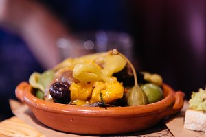 Green olives and yellow peppers in a ceramic bowl