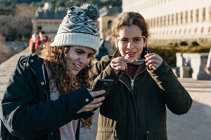 Happy teenage girls on of them in knit hat texting with cell pho
