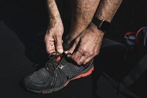Man putting on shoes before exercise