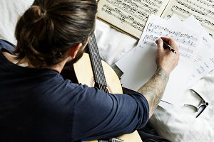 Man playing a guitar composing