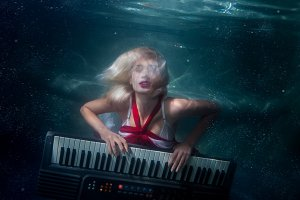 Woman plays music diving under the w