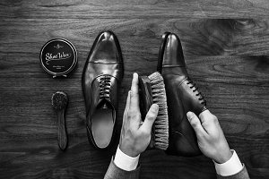Businessman cleaning his shoes