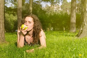 Woman with apple outdoors