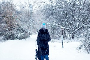 Woman with pram walking in winter