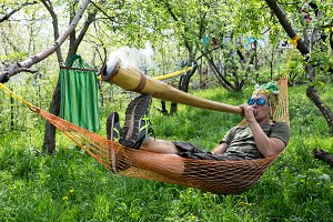 man in a hammock with  pipe
