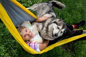 Happy girl with her dog resting in  hammock