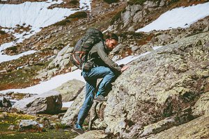 Travel Man with backpack climbing
