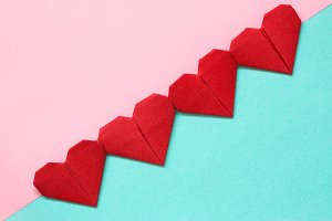 Red origami hearts on pink and blue