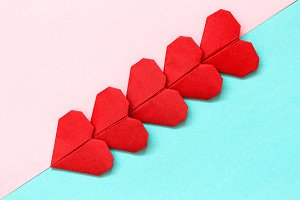 Red origami hearts lie diagonally on