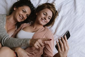 Friends chatting in the bedroom.