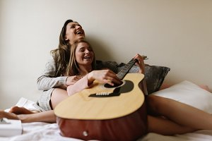 Gorgeous friends playing the guitar.