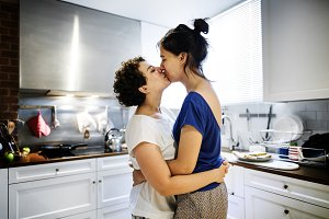 Lesbian couple kissing in kitchen