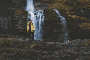 Hiker girl standing near waterfall