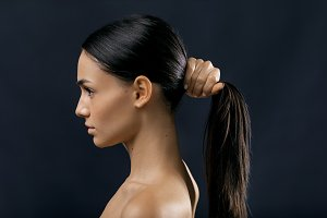 Side view of a woman holding hair