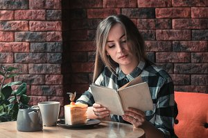Beautiful girl reads a book in a cafe