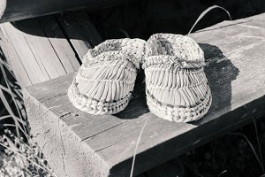 Wicker shoes on wooden doorstep at s