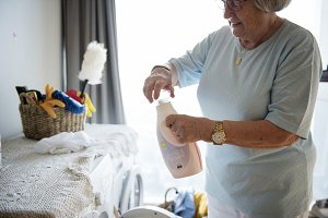 Elderly woman doing a laundry