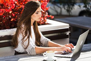 Beautiful brunette works with laptop