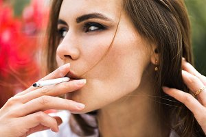 Brunette woman smokes a cigar