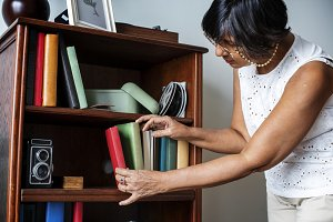 Senior woman cleaning the bookshelf