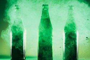 Three green bottles standing in a gr