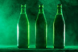 Three green beer bottles on a dusty