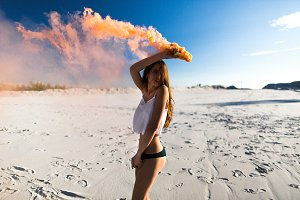 Woman dances with orange smoke