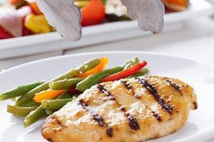 putting down grilled chicken