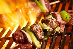 steak kabobs cooking on the grill