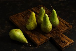 Green pears on a rustic  Board
